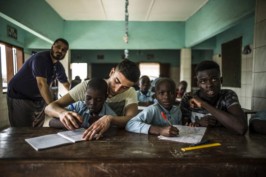 Programme de Cours accélérés de Cachi, avec l'athénée Alfred Verwée et Via Don Bosco.  Pendant que Kamal, à l'arrière-plan joue à l'éducateur (mais c'est son métier après tout), Emrah et Abdoulaye réapprennent les détails de la chaîne alimentaire avec les jeunes enfants.