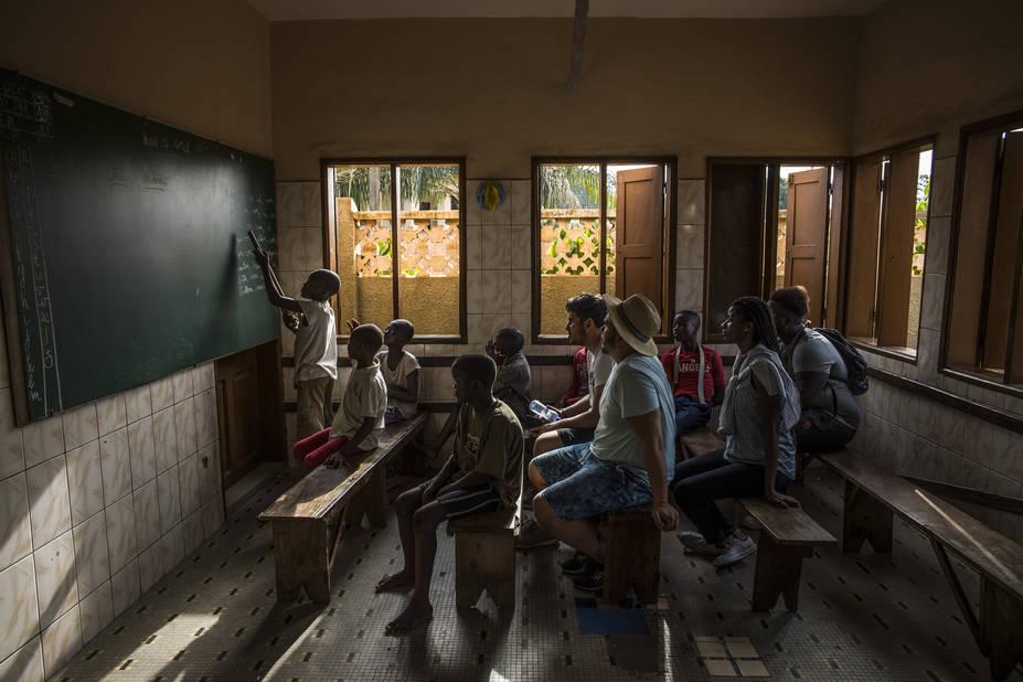 Momo Bilal, Tabita et N'gom suivent la leçon sur le verbe être avec les enfants en cours d'alphabétisation.