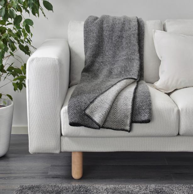 Plaid en laine gris clair d'un côté, gris foncé de l'autre. Ikea, 49,90€.