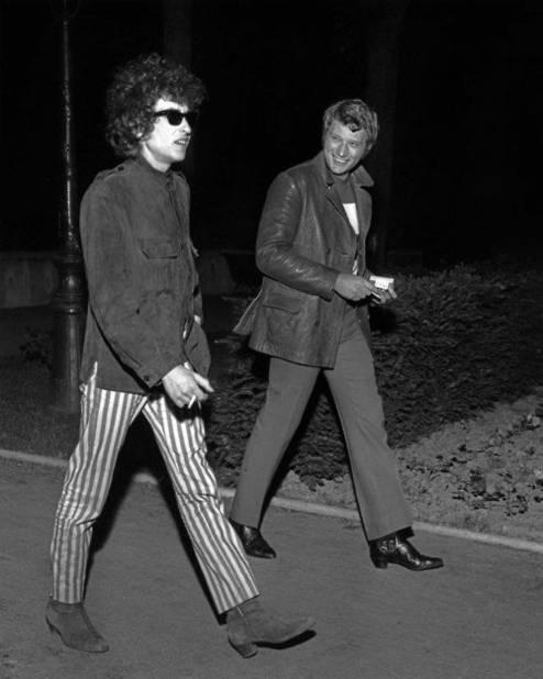 À partir de 1965, les rock stars se libèrent du costume. Elles vont s'habiller du côté de Carnaby Street, à Londres. Pantalon cigarette, veste d'inspiration militaire et chelsea boots sont de rigueur. Johnny est ici en compagnie de Bob Dylan, autre figure aussi incontournable que stylée à cette époque.
