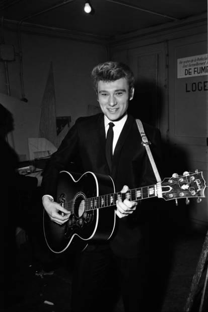 En backstage à l'Olympia en 1964, Johnny porte un costume cintré noir à revers fins qu'il accompagne d'une cravate slim. C'est le look du début des sixties par excellence. Nous sommes alors en pleine beatlemania. John, Paul, George et Ringo ont remis le costume au goût du jour et ils font des émules.