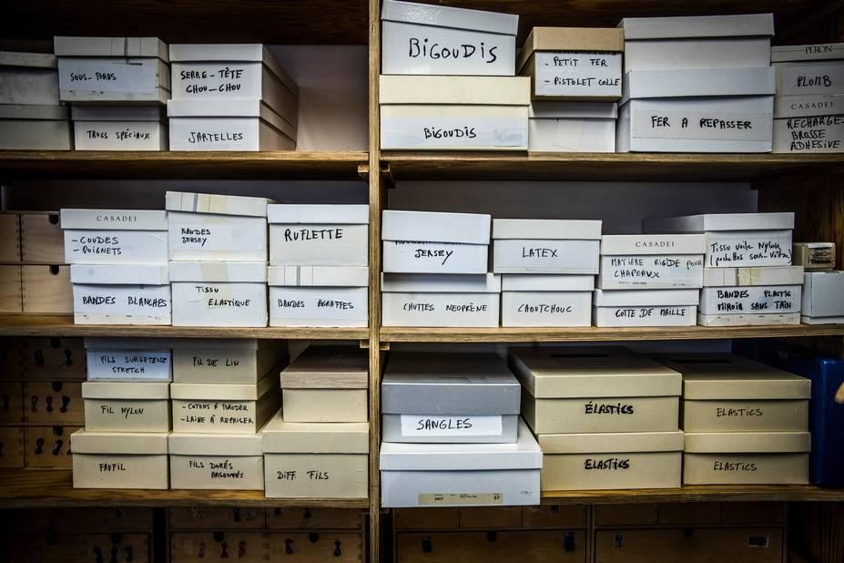 Des petites mains et des petites boîtes en carton, contenant des boutons, des lacets, des rubans, des élastiques, du latex, de la ruflette...