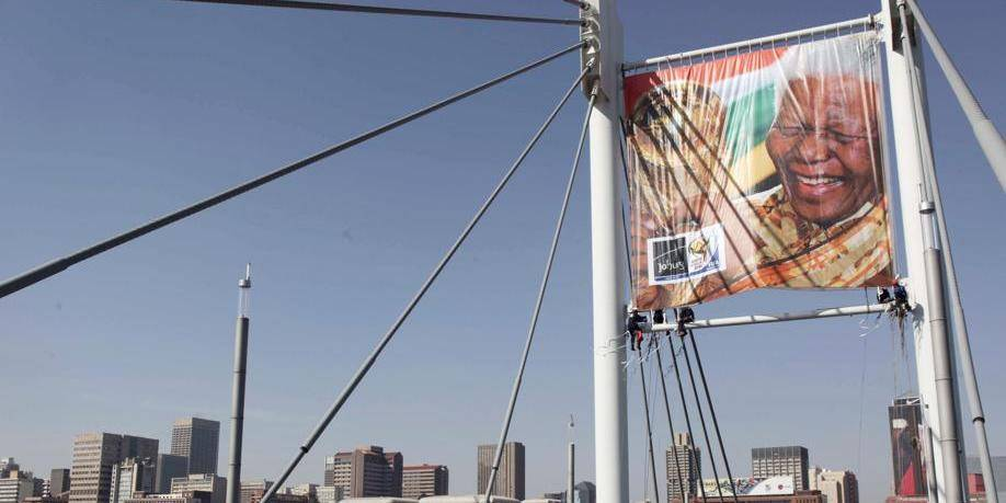 A giant banner with an image of former President Nelson Mandela with the World Cup Soccer trophy on the Nelson Mandela bridge in Johannesburg Friday June 4, 2010 ahead of the tournament which gets underway next Friday. (AP Photo/Denis Farrell) Associated Press / Reporters