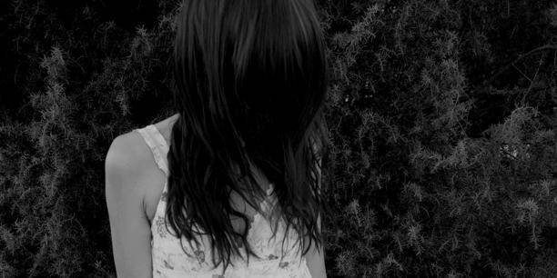 Young Woman In Dress Standing In Grass Hiding Her Face Behind Hair
