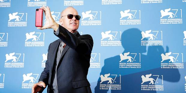 Actor Michael Keaton uses his mobile phone as he poses for photographers during a photo call for Birdman at 71st edition of the Venice Film Festival in Venice, Italy, Wednesday, Aug. 27, 2014. (AP Photo/David Azia)