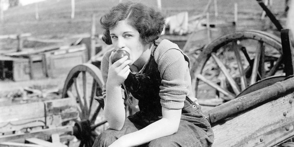 Young woman in working jeans sitting on wheel eating an apple Copyright: Reporters / Everett