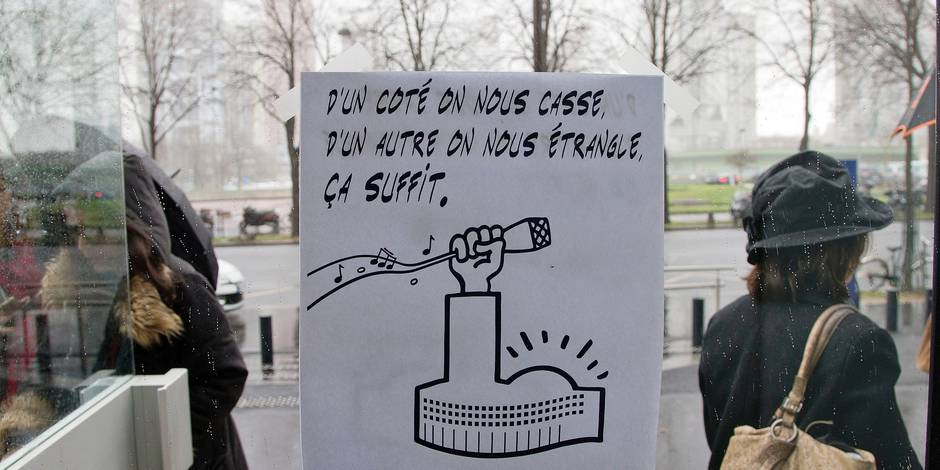 """A strike placard that reads: """"On one side they break us, on the other side, they strangle us. Enough"""" is stuck to an entrance at France's state radio corporation Radio France headquarters in Paris, France, Thursday, April 2, 2015. Journalists and media workers at Radio France have been on strike since Thursday, March 19 to oppose budget cuts and the potential cut of 300 jobs. (AP Photo/Francois Mori)"""