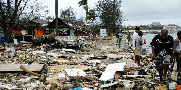 (150315) -- PORT VILA, March 15, 2015 () -- Locals walk past debris after Tropical Cyclone Pam wreaked havoc in Port Vila, Vanuatu, March 15, 2015. The cyclone-hit island nation of Vanuatu declared a state of emergency on Sunday after at least eight people were confirmed killed by Tropical Cyclone Pam, local press reported.(/Luo Xiangfeng)(dh) Reporters / Photoshot