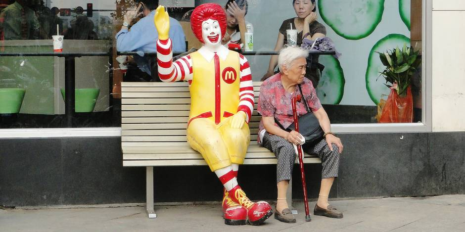 An elderly women sits next to Ronald MacDonald on a park bench in Wuxi, China in June 2009. The Canadian Press Images/Rob Skeoch.