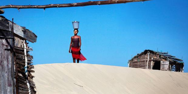 Madagascar, July 2011 Tulear, sarodrane a woman with a beauty mask walks with a bucket of water over the dunes
