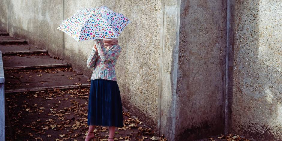 Woman holding spotty umbrella REPORTERS/Imagesource MODEL RELEASED