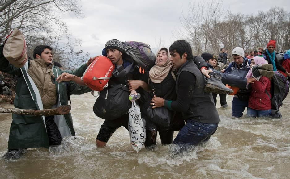 ***2e prix Contemporary Issue*** Singles  Une femme est portée lors de la traversée d'une rivière par des migrants pour rejoindre la Macédoine