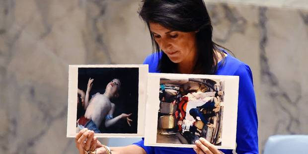 US Ambassador to the UN, Nikki Haley holds photos of victims as she speaks as the UN Security Council meets in an emergency session at the UN on April 5, 2017, about the suspected deadly chemical attack that killed civilians, including children, in Syria. / AFP PHOTO / TIMOTHY A. CLARY