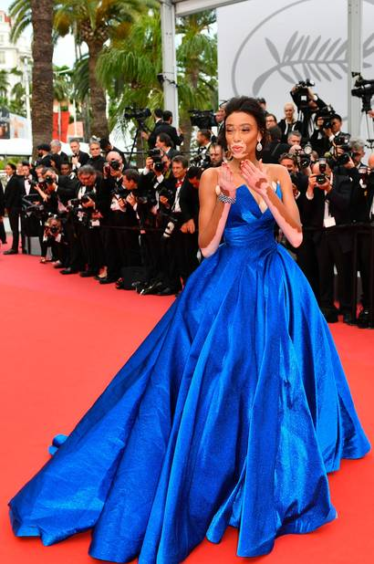 Le top model canadien Winnie Harlow dans une robe de princesse bleu électrique signée Zuhair Murad monte les marches pour la projection de Loveless.