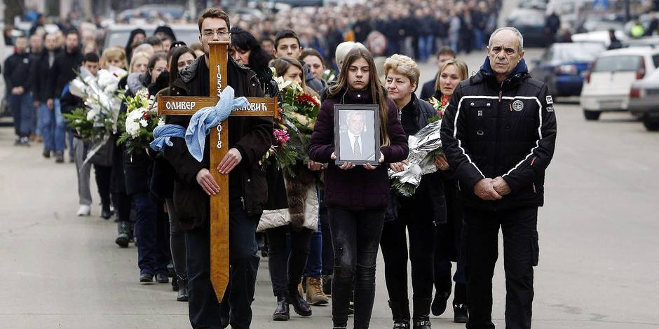 People carry flowers, a wooden cross and a portrait of assassinated prominent Kosovo Serb politician Oliver Ivanovic as they accompany the coffin of Ivanovic in Mitrovica on January 17, 2018 while investigators were probing the killing of a prominent Kosovo Serb politician, which observers warned could worsen tensions in the volatile region. Oliver Ivanovic, 64, was shot dead from a car on January 16, 2018 as he arrived at the headquarters of his party in the flashpoint town of Mitrovica in northern Kosovo. / AFP PHOTO / SASA DJORDJEVIC