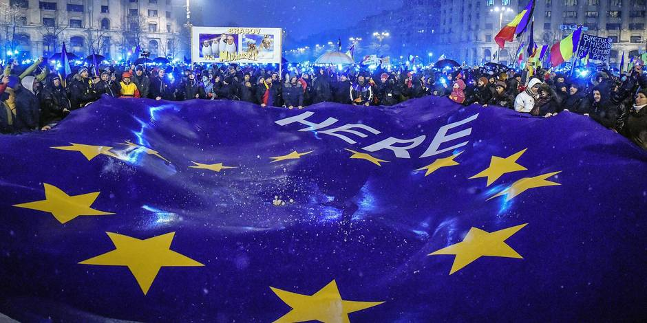 Demonstrators hold a giant flag of the European Union as they stage an anti-government and anti-corruption protest in front of the Romanian Parliament building in Bucharest January 20, 2018. More than 30,000 people in Bucharest and in other cities across the country demonstrated against the policy of the ruling social democratic PSD party and a new legislation that has sparked concerns in Brussels and Washington about the shaky government's commitment to fighting endemic corruption. / AFP PHOTO / Daniel MIHAILESCU