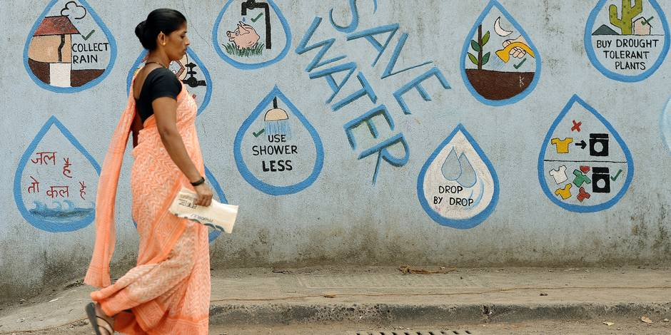 An Indian pedestrian walks past a wall adorned with water conservation messages in Mumbai on March 22, 2017, on World Water Day. Recycling the world's wastewater, almost all of which goes untreated, would ease global water shortages while protecting the environment, the United Nations said in a major report. / AFP PHOTO / PUNIT PARANJPE