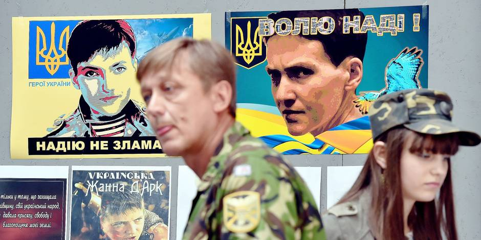"""A Ukrainian serviceman and a girl wearing military fatigues, walk in front of placards bearing pictures of Nadezhda (Nadia) Savchenko and reading """"Free Nadia!"""", """"Nadia can not be broken"""" and """"Nadia is Ukrainian Joan of Arc"""" on the opening day of the exhibition dedicated to Savchenko in Kiev on June 19, 2015. Russia charged in April 2015 Ukrainian airforce officer Nadia Savchenko over the deaths of two Russian journalists in a politically charged case that has become emblematic of tensions between Kiev and Moscow. Considered a symbol of resistance against what most Ukrainians call a Russian-created insurgency, she was even elected to parliament in absentia. AFP PHOTO/ SERGEI SUPINSKY / AFP PHOTO / SERGEI SUPINSKY"""