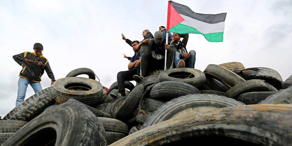 ©Ashraf Amra \ apaimages/MAXPPP - Khan Yunis ; Palestinian Territory - Palestinian protesters sit on a pile of tires during a tent city protest along the Israel border with Gaza, demanding the right to return to their homeland, in Khan Yunis in the southern Gaza Strip April 3, 2018. Photo by Ashraf Amra