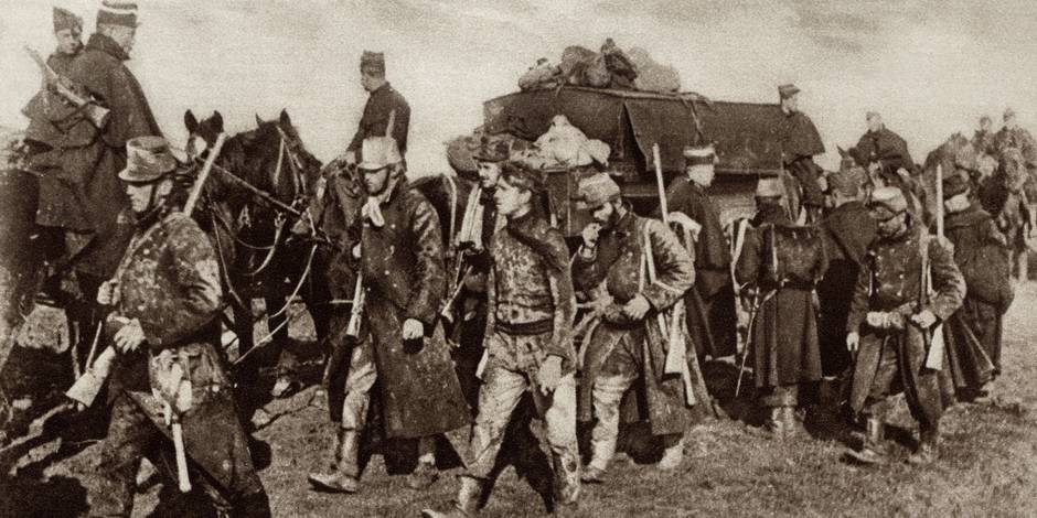 World War 1. Belgian troops, weary and mud-covered from fighting in the trenches moving forward to take up a new position near Veurne. 1914.