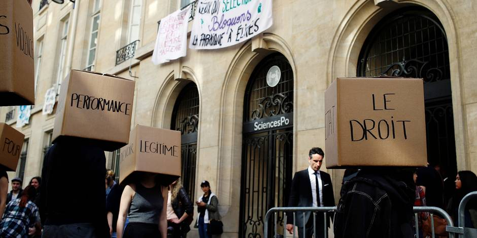 "Students wearing boxes reading ""Performance, Legitimate, The Rights"" perform in front of a blocked entry at the Institute of Political Studies(IEP) or Sciences Po, in Paris, France, Wednesday, April 18, 2018. French students intensified blockades of universities over the government's reform. (AP Photo/Francois Mori)"